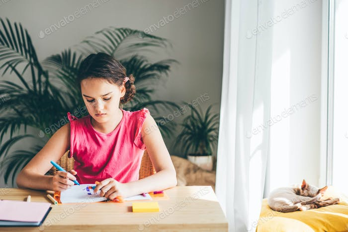 Chica caucásica sentada en el escritorio y escribiendo en un cuaderno y haciendo la tarea.