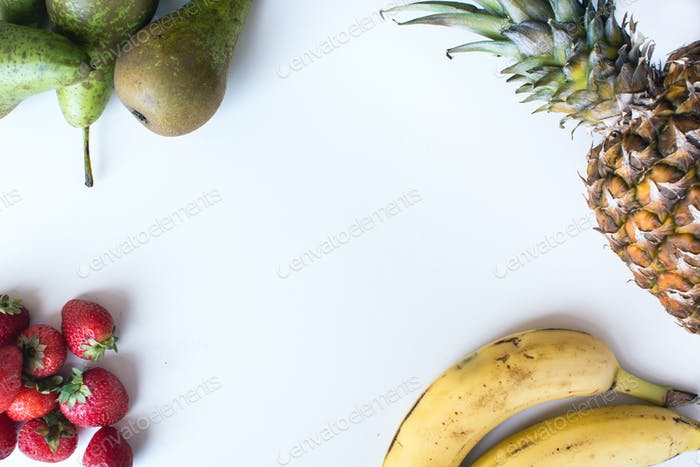 Aerial shot of fresh bananas, pears, strawberries and pineapple on a white background