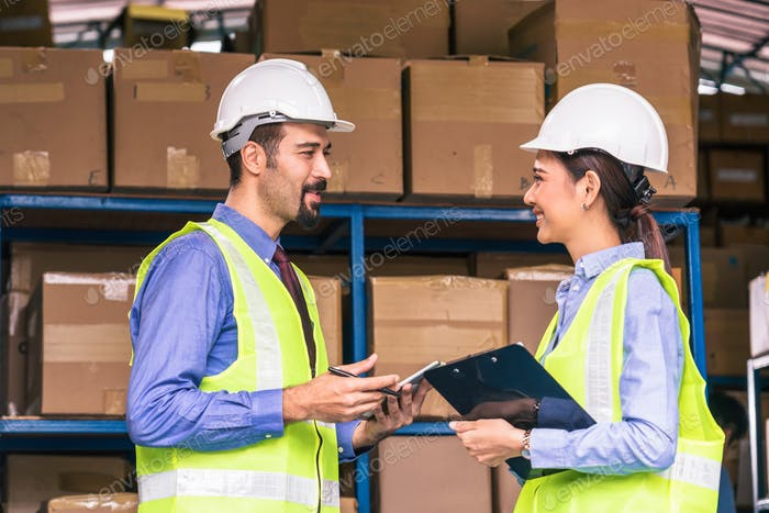 White Caucasian Manager of warehouse working and discussing with Asian assistant manager