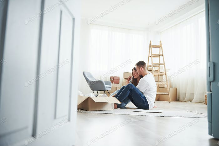 Empty room with boxes and ladder. Cheerful young couple in their new apartment. Conception of moving