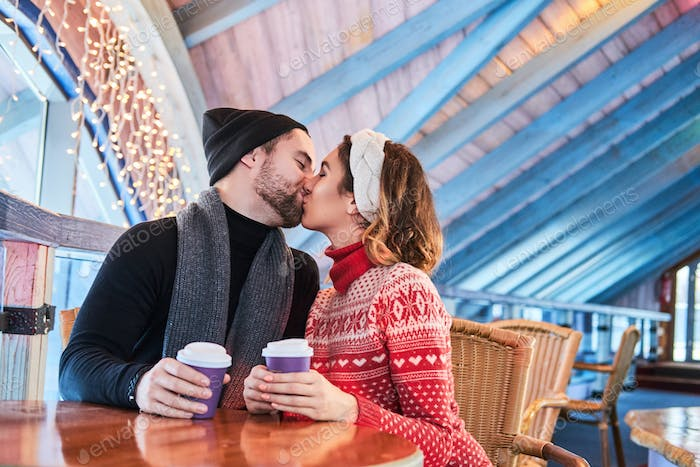 Young couple on a date in cafe, talking and kissing at Christmas time