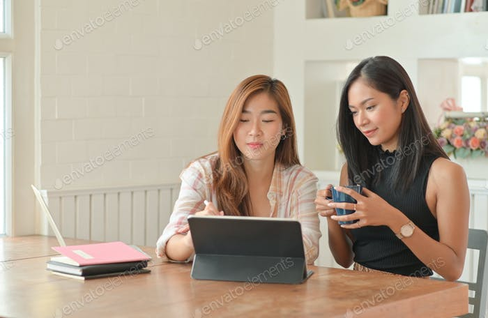 Two young female students with coffee are using laptop to study online at home.