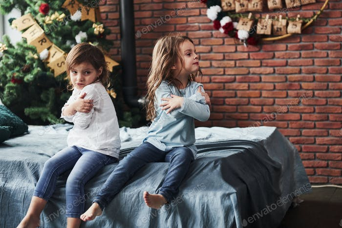 Offended at each other. Kids in the beautiful room at new year having some bad mood