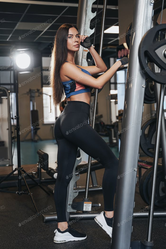 Young sportive woman staying near barbell in sport club