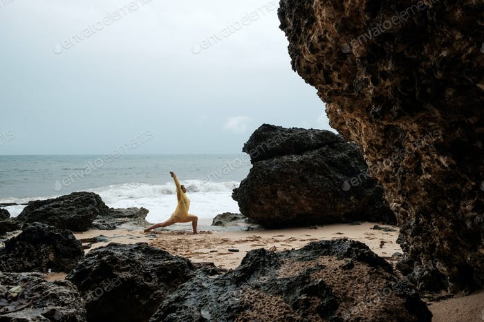 Woman in rain coat doing balance yoga asana on ocean beach during storm.