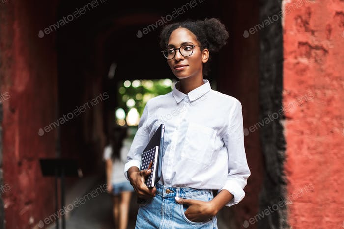 Pretty african girl in eyeglasses and shirt holding laptop and n