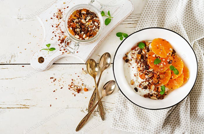 Bowl of homemade granola with yogurt and tangerine on white wooden table. Fitness food. Top view