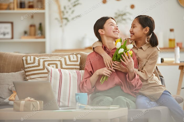 Daughter Giving Flowers To Mom