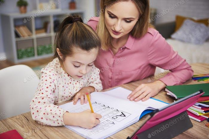 Junge Frau helfen Mädchen mit Hausaufgaben