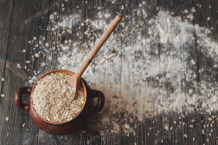 Topf mit einem Löffel voller Getreide und auf rustikalem Hintergrund. Ansicht von oben