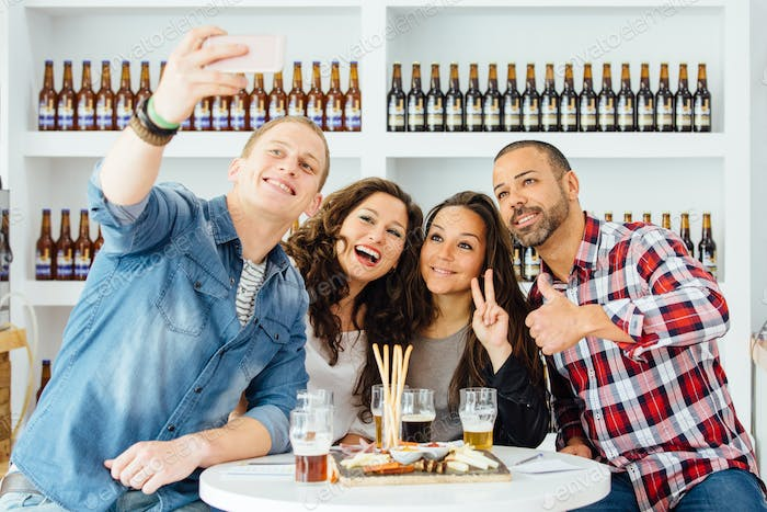 Cheerful people taking selfie with in bar