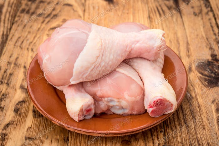 raw chicken legs on wooden table