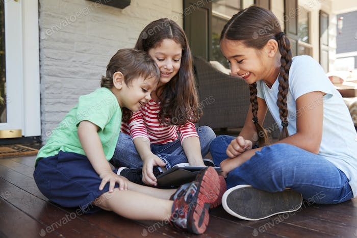 Group Of Children Sit On Porch Playing With Digital Tablet