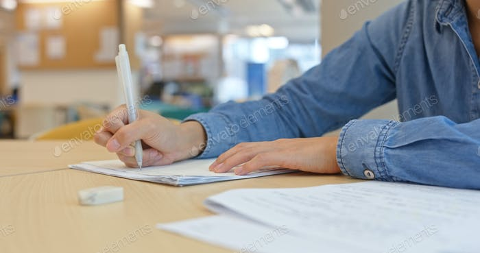 Woman write on the paper with cellphone at home