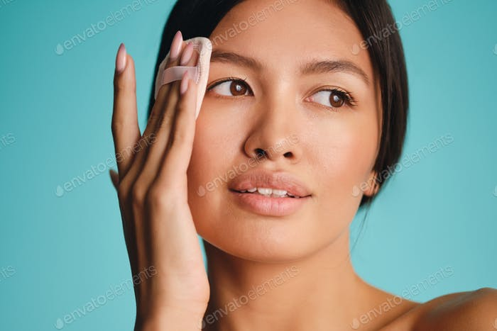Close up attractive young Asian brunette woman happily looking away using powder puff