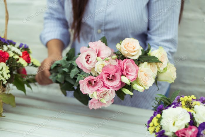 Female florist making beautiful bouquet at flower shop