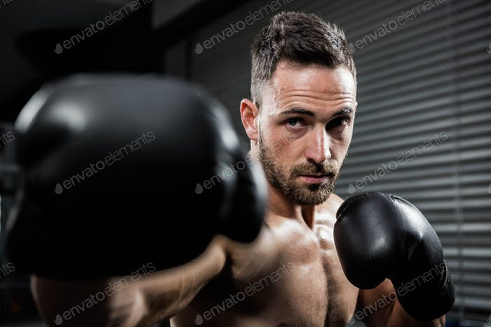 Determined shirtless man with boxe gloves hitting at crossfit gym