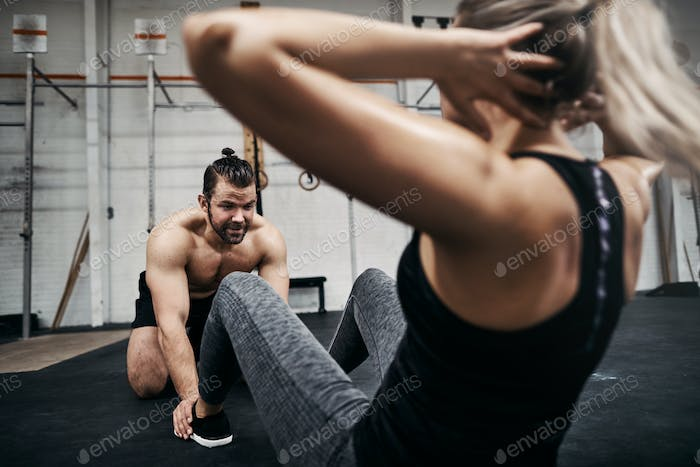 Fit woman doing sit ups with a male gym partner
