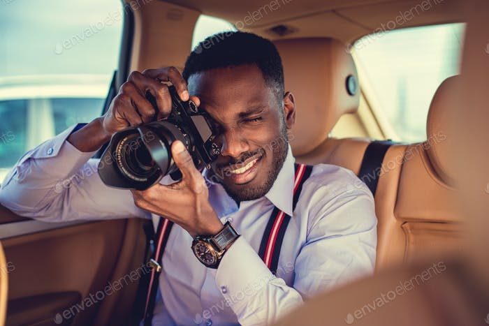 A black man using dslr camera in a car.