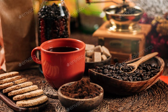 Red Coffee Cup, Coffee Beans And Ground Coffee In Wooden Bowl