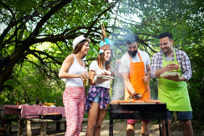 Friends having a barbecue party in nature while having fun