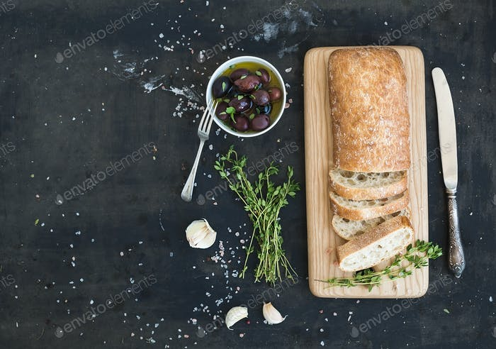 Italian ciabatta bread cut in slices on wooden chopping board with herbs, garlic and olives