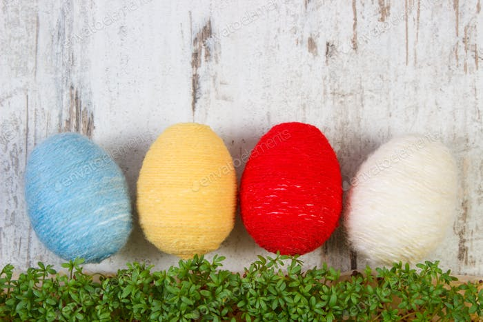 Easter eggs wrapped woolen string and green cress, copy space for text, decoration for Easter