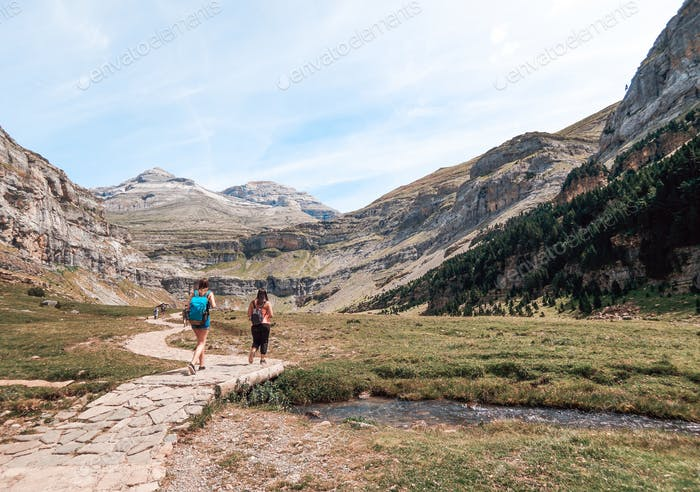Two young woman walking on Ordesa and Monte Perdido hiking trail in Huesca, Spain