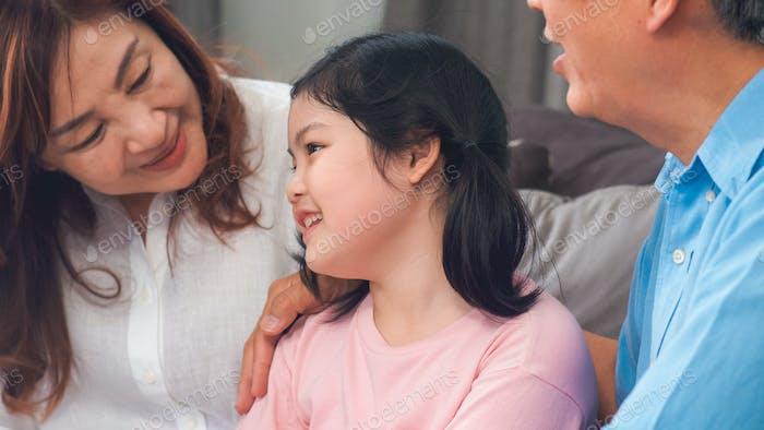 Asiatische Großeltern sprechen zu Hause mit Enkelin.