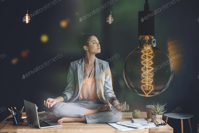 light bulb representing creative thinking and young businesswoman meditating in lotus position on