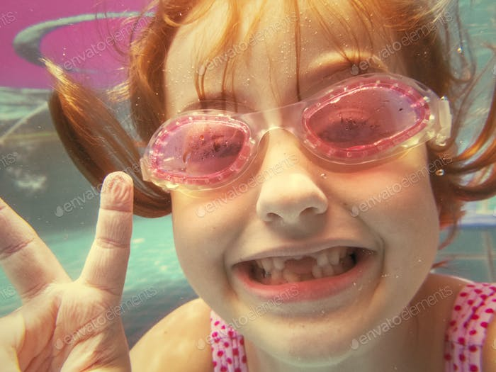 Girl with goggles diving in swimming pool