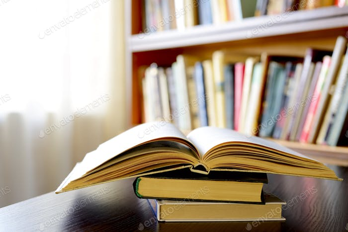 Ein offenes Buch mit Bücherregalen im Hintergrund