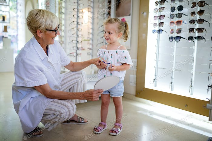Optician mature woman and little girl choosing glasses at optics store