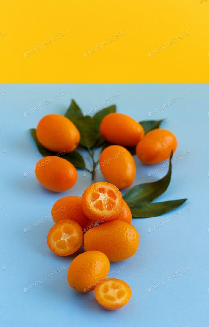 Kumquat Früchte auf einem blauen und gelben Hintergrund