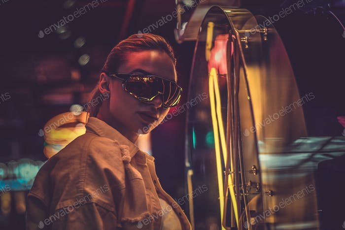 Attractive stylish woman is posing for photographer in neon lights