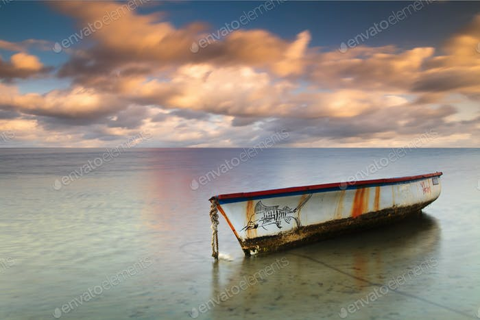 Boat on a tropical island with a beautiful sunset sky background.