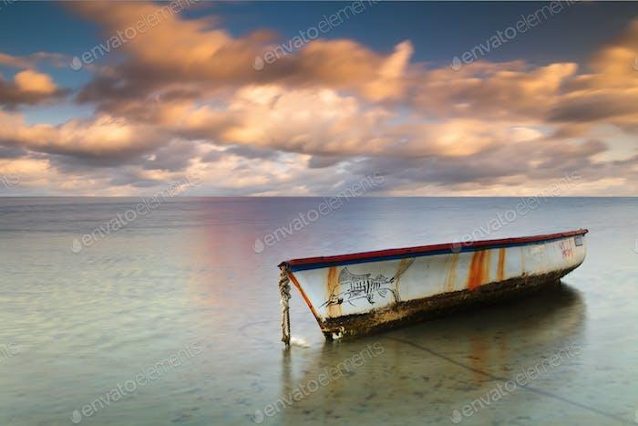 Boot auf einer tropischen Insel mit einem schönen Sonnenuntergang Himmel Hintergrund.