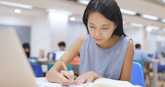 Frau arbeitet an Hausaufgaben in der Bibliothek