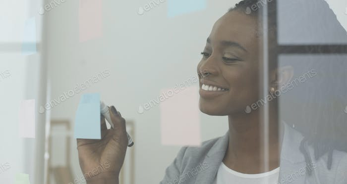 African American Girl Writing Notes On Glass Visualisation Board Indoor