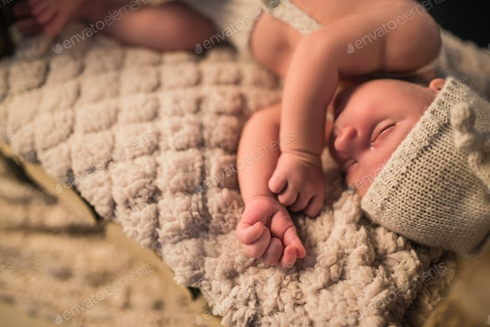 Little charming newborn baby in a knitted suit