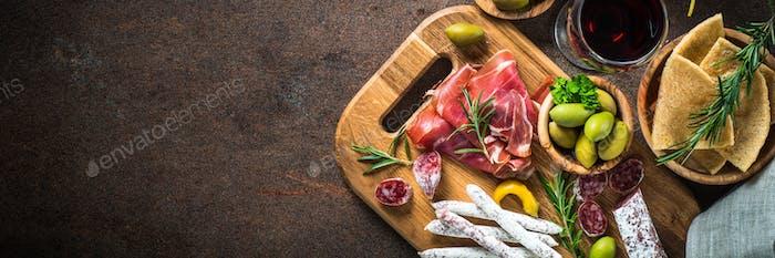 Antipasto - sliced meat, ham, salami, olives and wine  top vie