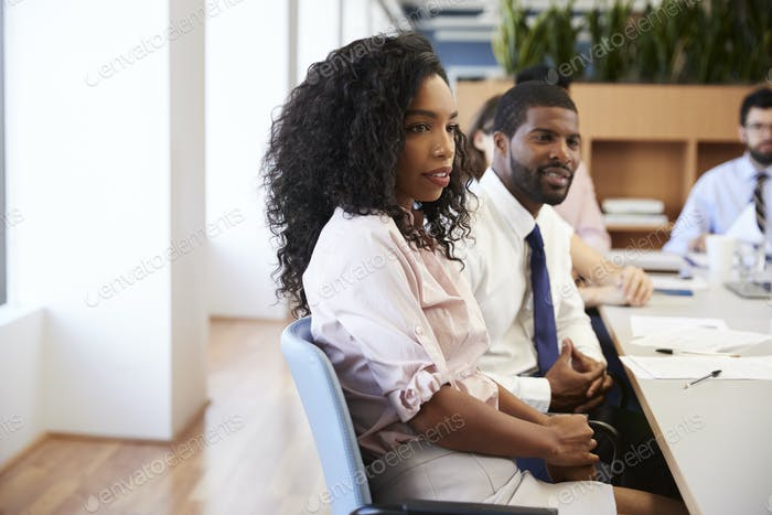 Businesswoman With Colleagues Sitting At Table Listening To Presentation In Modern Office