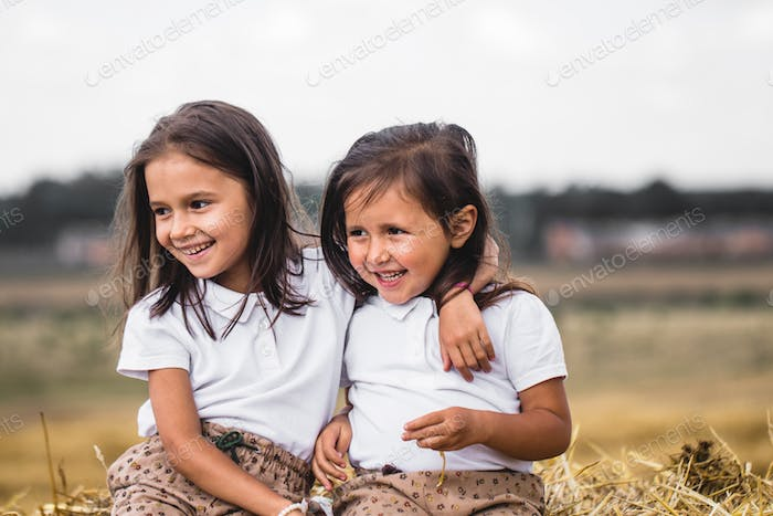 Two girls sitting on a bale of hay