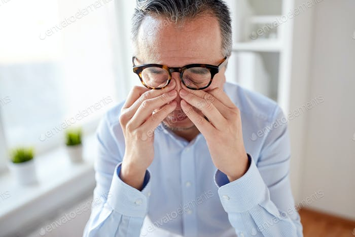 businessman in glasses rubbing eyes at office