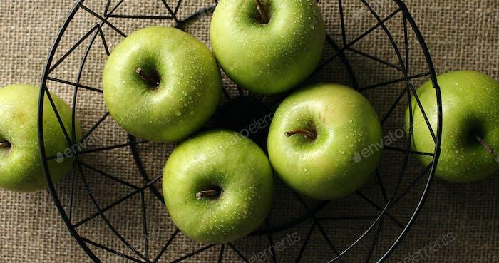 Green wet apples in vase