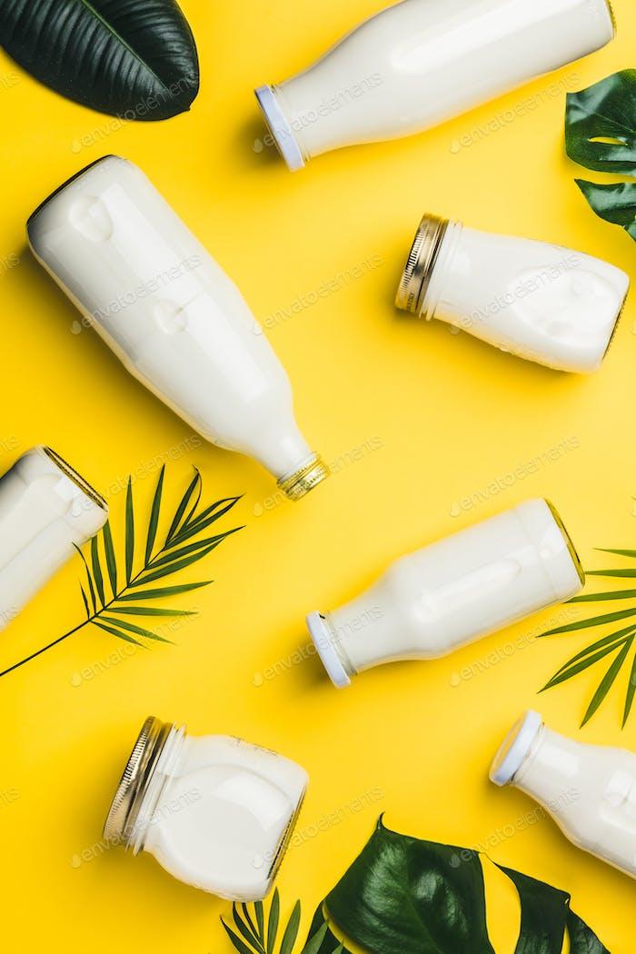 Verschiedene Flaschen Milch und tropische Blätter