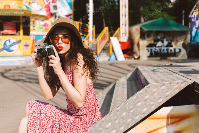 Beautiful lady in sunglasses and hat spending time in amusement park with little camera