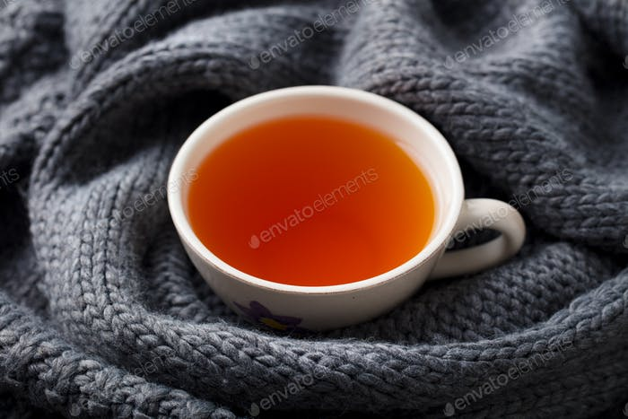 Cup of tea. Grey knitted scarf background. Close up.