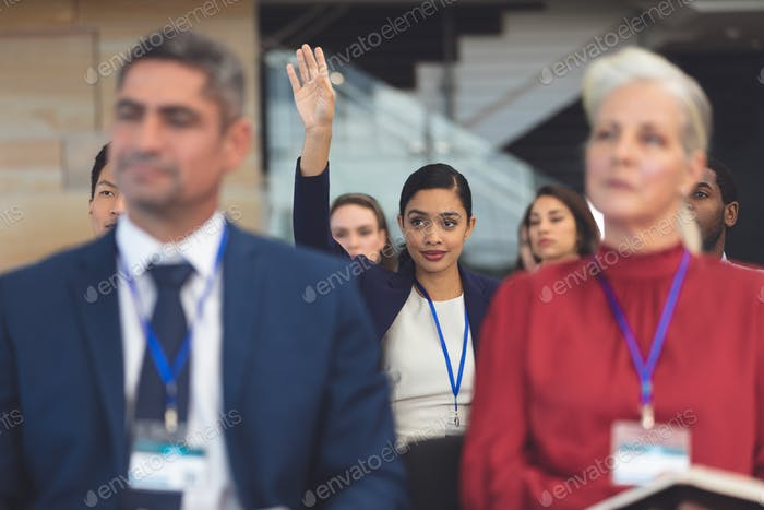 Front view of young mixed race businesswoman raising hand in a business seminar in conference