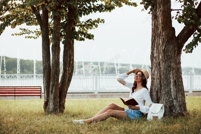 Inspiring book. Young woman have weekend and sits in the park at daytime